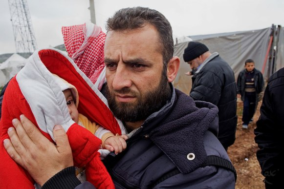 March 16, 2012- Reyhanli, Turkey: A Syrian man holds his son who is bundled up against the the cold in the Reyhanli refugee camp in Hatay province on the Turkish/Syrian border on Friday March 16, 2012.