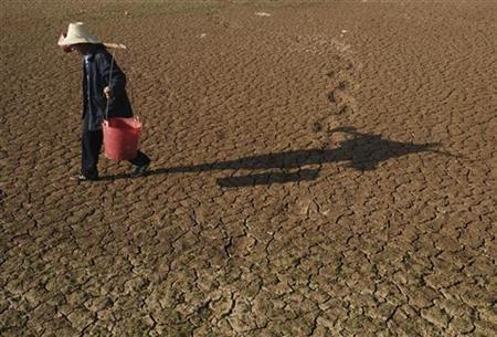 A farmer carries buckets to collect water as he walks on a dried-up pond on the outskirts of Yingtan